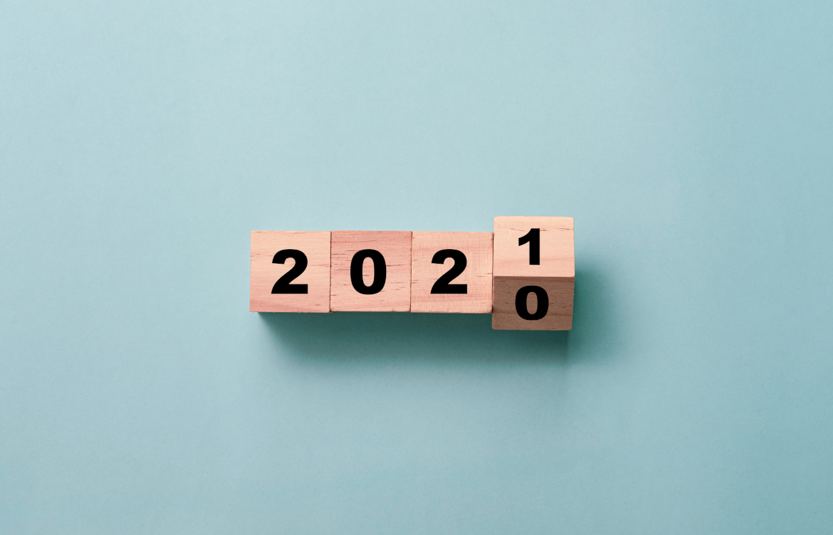 The year 2021 spelled out with wooden cubes, with the cube displaying 1 mid-way through rotating off of 0