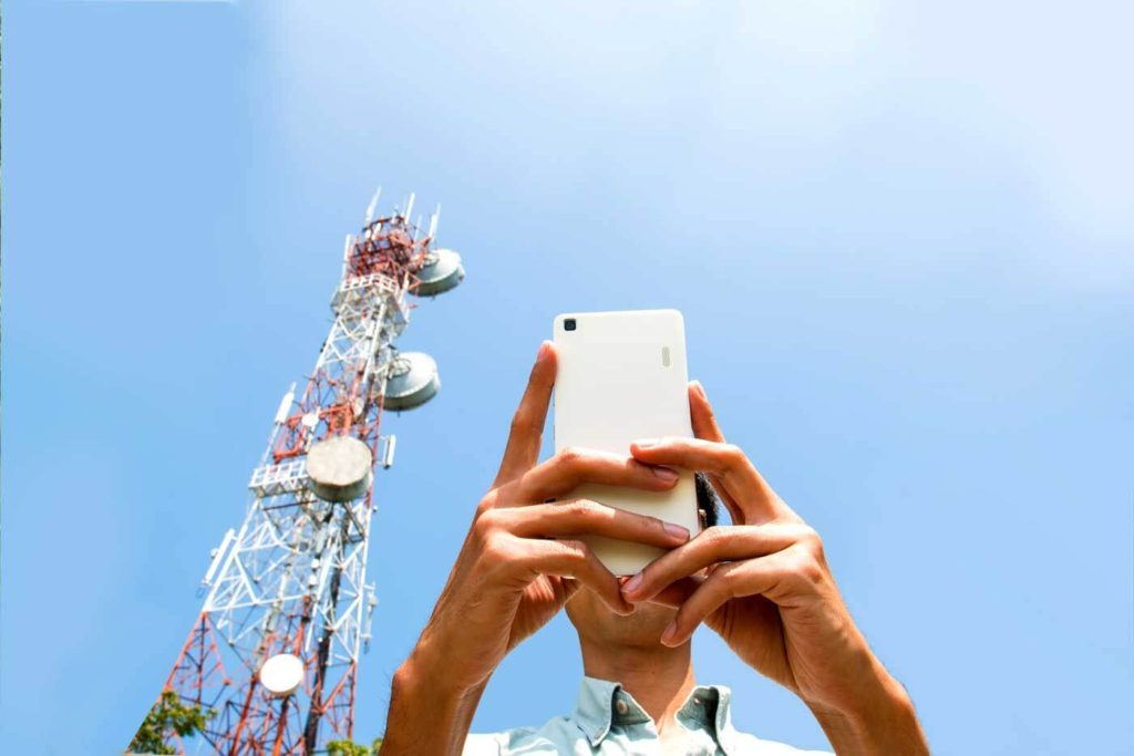 Man using a mobile phone in front of a cellular tower