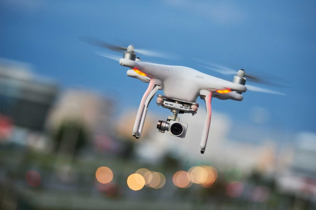 Close up of a flying drone with a blurred cityscape in the background