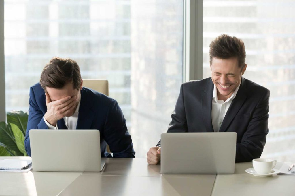 Two businessmen sitting a table with laptops laughing