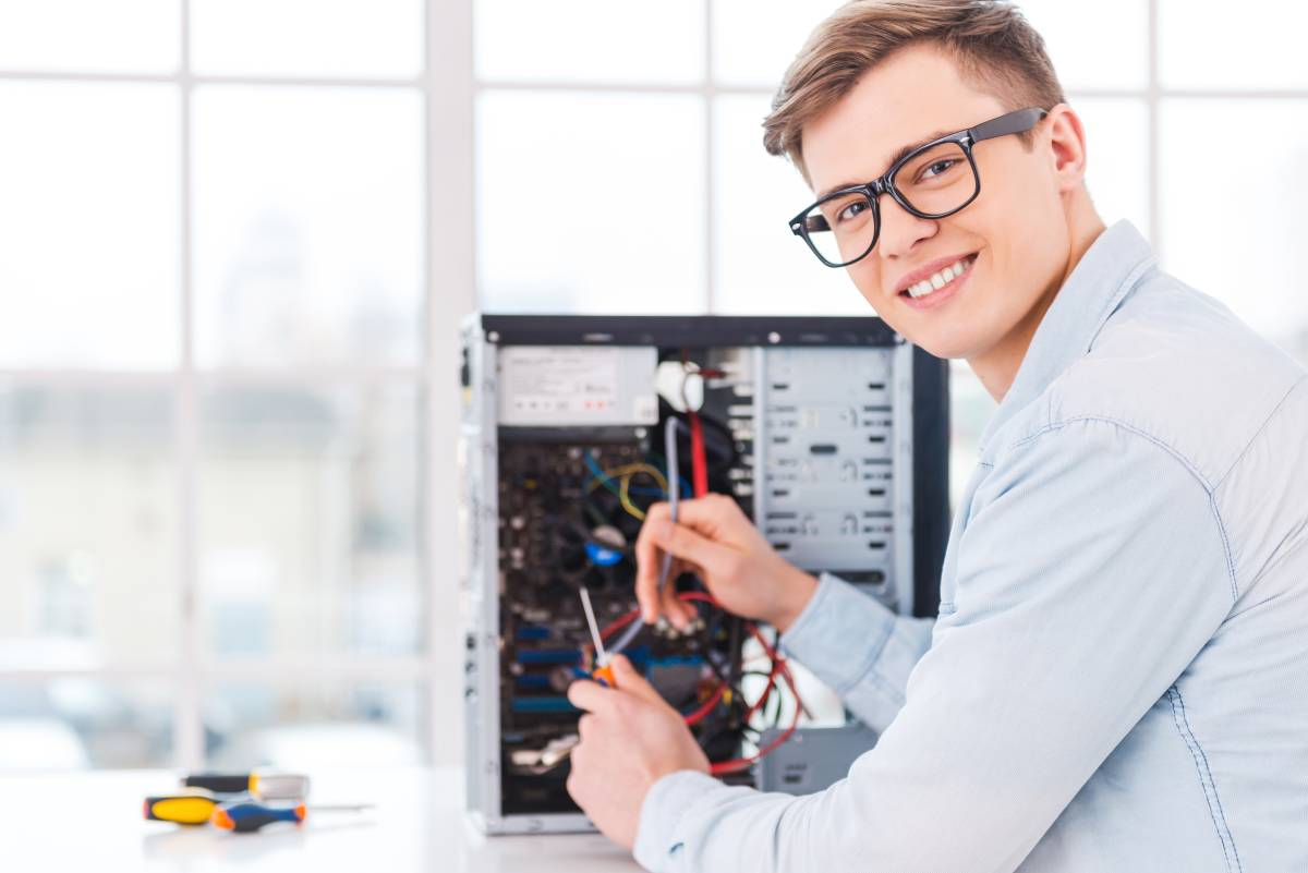 A technician working on a computer and smiling at the camera