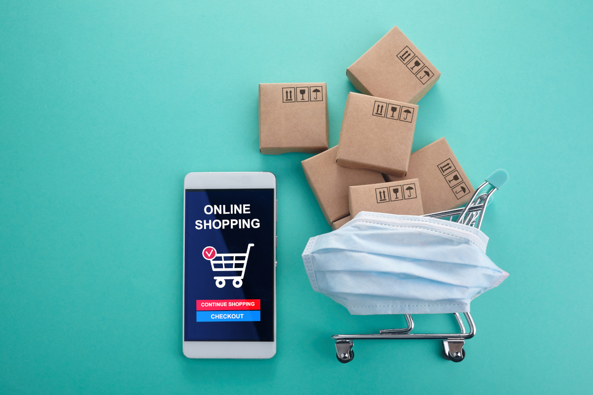 Phone with 'Online Shopping' on Screen and Shopping Cart in Surgical Mask Filled with Delivery Boxes