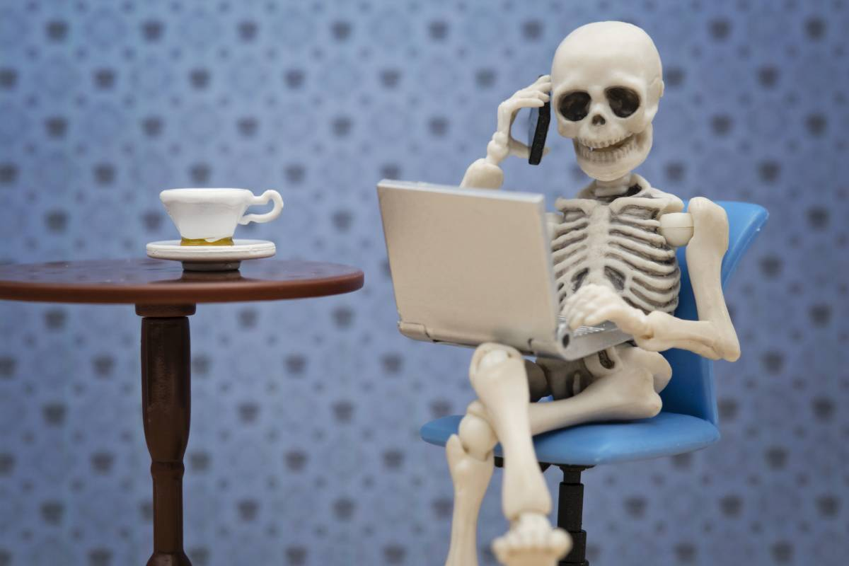A skeleton using a laptop and talking on the phone